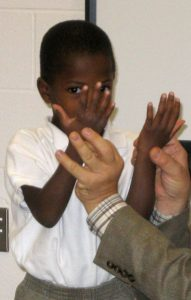 Teacher holding student's hands
