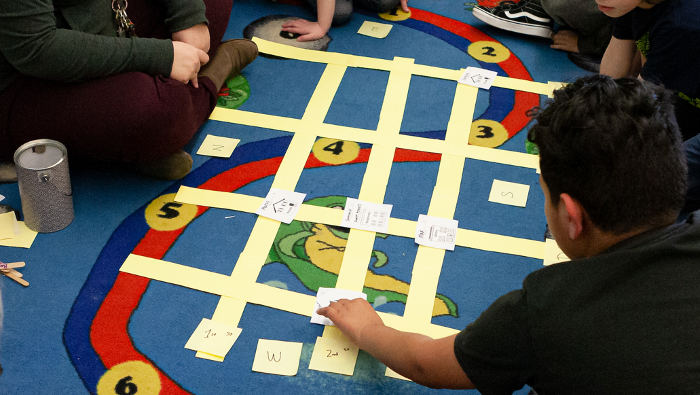 photograph of map made of paper strips on the rug, with children sitting around
